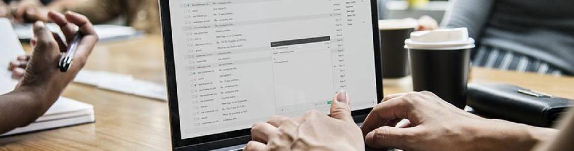 Eine Person schreibt in einem Meeting eine Textnachricht auf Ihrem Laptop.
