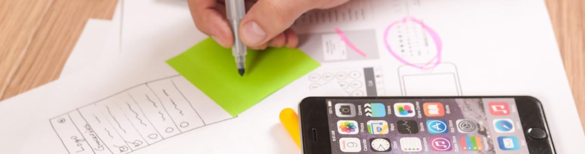 Eine Person macht Notizen auf einem Post-It. Neben Ihrer Hand liegt ihr Smartphone, unter dem Post-It einige weitere Notizen.