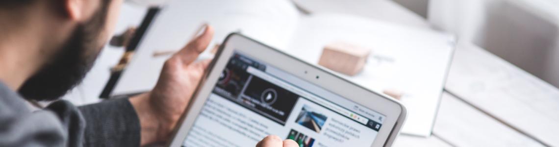 Ein Mann, der auf einem iPad durch eine Webseite scrollt.